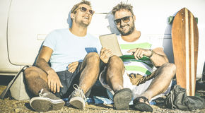 Hipster best friends having fun with tablet at car trip moment. Modern friendship and technology concept with always connected young people at alternative Stock Photos