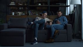 Hipster best friends with smartphones on the couch