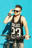 Hipster with a bike  near a bright blue wall. Smile Stock Image