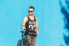 Hipster with a bike  near a bright blue wall. Smile Royalty Free Stock Photo