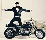 Hipster biker brutal in leather jacket on motorcycle enjoying richness. Superiority concept. Man, bearded biker in. Leather jacket near motor bike in luxury Royalty Free Stock Photo