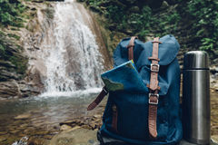 Hipster Blue Backpack, Map And Thermos Closeup. View From Front Tourist Traveler Bag On Waterfall Background. Adventure Hiking Con Royalty Free Stock Photo