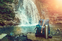 Hipster Blue Backpack, Map And Thermos. View From Front Tourist Traveler Bag On Waterfall Background. Wanderlust Adventure Hiking Stock Photo