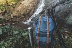 Hipster Blue Backpack, Thermos And Trekking Poles Closeup. View From Front Tourist Traveler Bag On Waterfall Background. Adventure Stock Photography