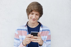 Hipster boy holding smart phone typing messages to his girlfriend having pleased expression telling her about his love. Cheerful t stock photos
