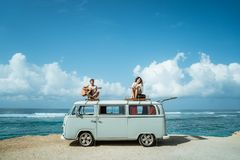 Hipster boy playing guitar with girlfriend on top of retro style. D minivan enjoy freedom song royalty free stock photo