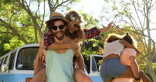 Hipster boys carrying girls on their shoulders stock video footage