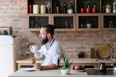 Hipster breakfast contemplation man coffee loft. Hipster breakfast. New day. Contemplation. Bearded man with cup of coffee and croissant looking sideways. Loft stock image