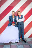 Hipster bride and groom posing against red striped wall Royalty Free Stock Photos