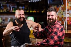 Hipster brutal bearded man drinking alcohol with friend at bar counter. Men drunk relaxing at pub having fun. Strong. Hipster brutal bearded men drinking alcohol stock photo