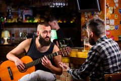 Hipster brutal bearded spend leisure with friend in bar. Real men leisure. Cheerful friends relax with guitar music. Man royalty free stock photography
