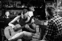 Hipster brutal bearded spend leisure with friend in bar. Real men leisure. Man play guitar in bar. Friday relaxation in stock images