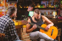 Hipster brutal bearded spend leisure with friend in bar. Real men leisure. Man play guitar in bar. Friday relaxation in. Bar. Friends relaxing in bar or pub royalty free stock photo