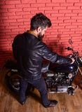 Hipster, brutal biker in leather jacket sits down on motorcycle, rear view. Man with beard, biker in leather jacket near. Motor bike in garage, brick wall Stock Images