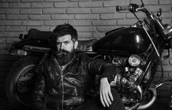 Hipster, brutal biker on pensive face in leather jacket sits, leans on motorcycle. Bikers lifestyle concept. Man with. Beard, biker in leather jacket near motor Stock Image