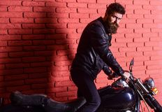 Hipster, brutal biker on serious face in leather jacket gets on motorcycle. Man with beard, biker in leather jacket near. Motor bike in garage, brick wall Stock Photo