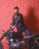 Hipster, brutal biker on serious face in leather jacket gets on motorcycle. Man with beard, biker in leather jacket near. Motor bike in garage, brick wall stock images