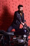 Hipster, brutal biker on serious face in leather jacket gets on motorcycle. Masculine passion concept. Man with beard. Biker in leather jacket near motor bike Royalty Free Stock Photo