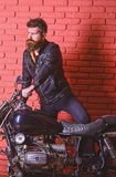 Hipster, brutal biker on serious face in leather jacket gets on motorcycle. Masculine passion concept. Man with beard. Biker in leather jacket near motor bike royalty free stock image