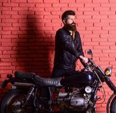 Hipster, brutal biker on serious face in leather jacket gets on motorcycle. Start of journey concept. Man with beard. Biker in leather jacket near motor bike Stock Photos