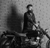 Hipster, brutal biker on serious face in leather jacket gets on motorcycle. Start of journey concept. Man with beard. Biker in leather jacket near motor bike royalty free stock photo