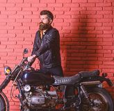 Hipster, brutal biker on serious face in leather jacket gets on motorcycle. Start of journey concept. Man with beard. Biker in leather jacket near motor bike stock photo