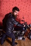 Hipster, brutal biker on strict face in leather jacket sits down on motorcycle. Man with beard, biker in leather jacket. Near motor bike in garage, brick wall Royalty Free Stock Photography