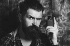 Hipster posing with black perfume or cologne bottle. Hipster or brutal caucasian man with grey hair, long beard and moustache posing with black perfume or stock images