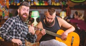 Hipster brutale gebaard met vriend in bar De gitaar van het mensenspel in bar De vrolijke vrienden zingen de muziek van de liedgi stock afbeeldingen