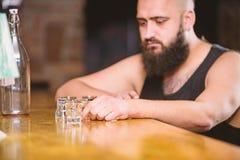 Hipster brutale mens het drinken alcohol die tot meer dranken opdracht geven bij barteller Alcoholisme en depressie De kerel best royalty-vrije stock afbeelding