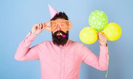 Hipster with bushy beard celebrating birthday. Bearded man posing in birthday cap with enormous glasses and bright. Balloons isolated on blue background. Man Stock Image