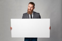 Hipster business man. With beard and mustashes in suit standing holding white banner, looking away over grey background stock photography