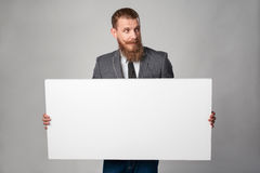 Hipster business man. With beard and mustashes in suit standing holding white banner, looking away with over grey background royalty free stock photos