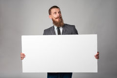 Hipster business man. With beard and mustashes in suit standing holding white banner, looking up over grey background stock image