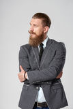 Hipster business man looking to side. Confident stylish business man with beard and mustashes in suit standing with folded hands looking to the side at blank stock images
