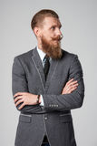 Hipster business man looking to side. Confident stylish business man with beard and mustashes in suit standing with folded hands looking to the side over grey royalty free stock photography