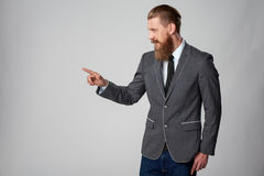 Hipster business man looking to side. Confident stylish business man pointing to side, pressing imaginary button at blank copy space over grey background Stock Image