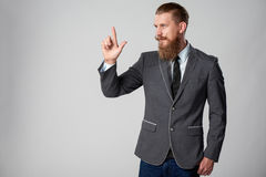 Hipster business man looking to side. Confident stylish business man pointing to side, pressing imaginary button at blank copy space over grey background Royalty Free Stock Photos