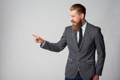 Hipster business man looking to side. Confident stylish business man pointing to side, pressing imaginary button at blank copy space over grey background Stock Photography