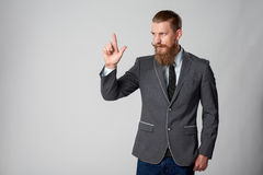 Hipster business man looking to side. Confident stylish business man pointing to side, pressing imaginary button at blank copy space over grey background Stock Images