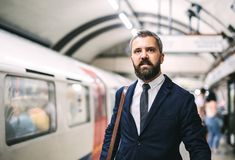 Hipster businessman with a bag waiting for the train in subway. royalty free stock photos