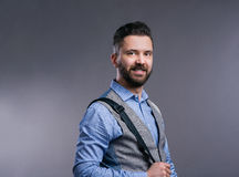 Hipster businessman in blue shirt, studio shot, gray background Royalty Free Stock Image