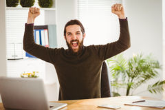 Hipster businessman cheering at his desk Royalty Free Stock Image