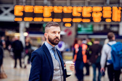 Hipster businessman with coffee cup at the train station Royalty Free Stock Photos