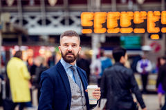 Hipster businessman with coffee cup at the train station Royalty Free Stock Image