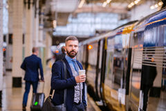 Hipster businessman with coffee cup at the train station Royalty Free Stock Photo