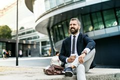 Hipster businessman with coffee sitting outdoors in the city. stock photos