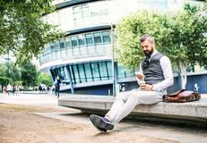 Hipster businessman with coffee and smartphone sitting outdoors in the city. stock images