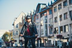 Hipster businessman commuter with electric bicycle traveling home from work in city. Copy space royalty free stock photo