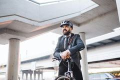 Hipster businessman commuter with electric bicycle traveling home from work in city. Hipster businessman commuter with electric bicycle traveling home from work royalty free stock image